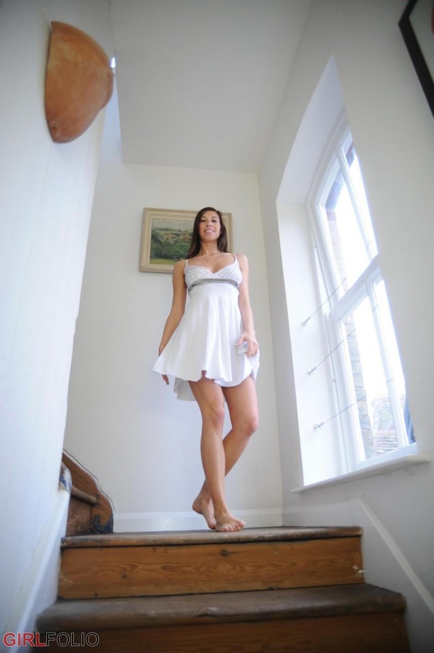 Длинноногая брюнетка в коротком платье позирует на лестнице и нежно ласкает красивую грудь второго размера