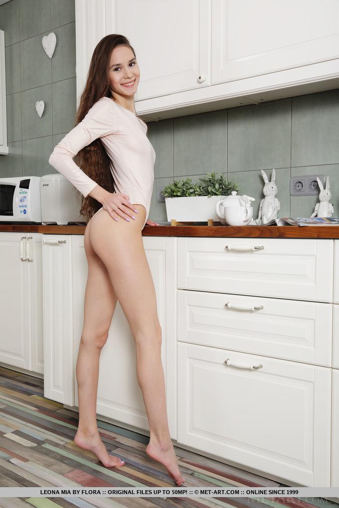 Худая брюнетка в обтягивающем боди наслаждается своим телом на кухне и мастурбирует лежа на полу в разных позах