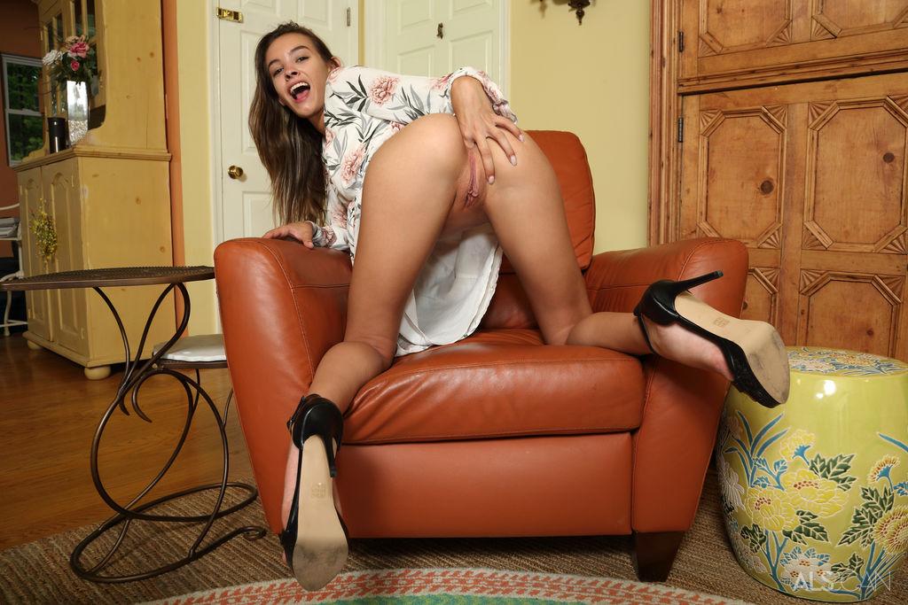 Худышка на высоких каблуках позирует совершенной голой и сидя в кресле пальцами растягивает вагинальную дырку