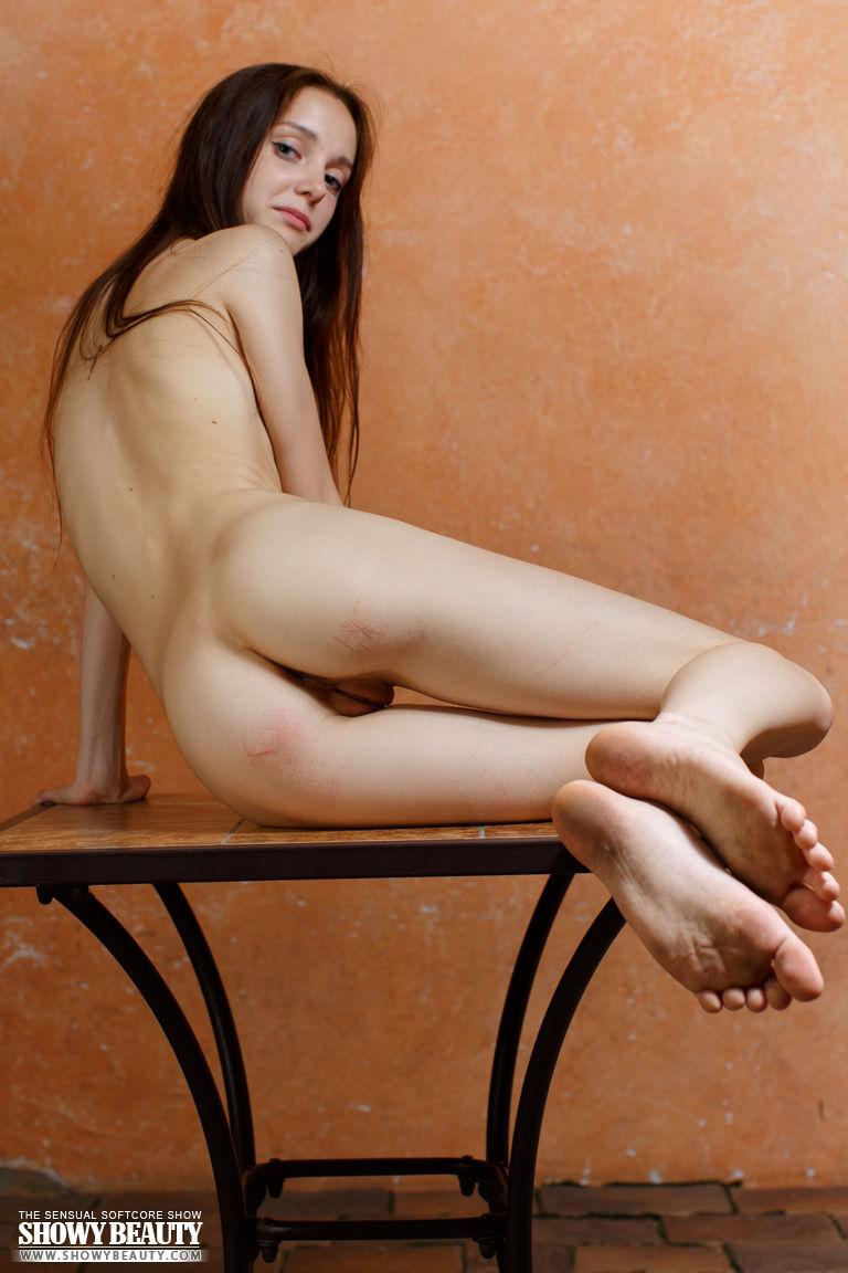 Худышка с распущенными волосами ложится на стол и раздвигает ноги крупным планом перед скрытой камерой