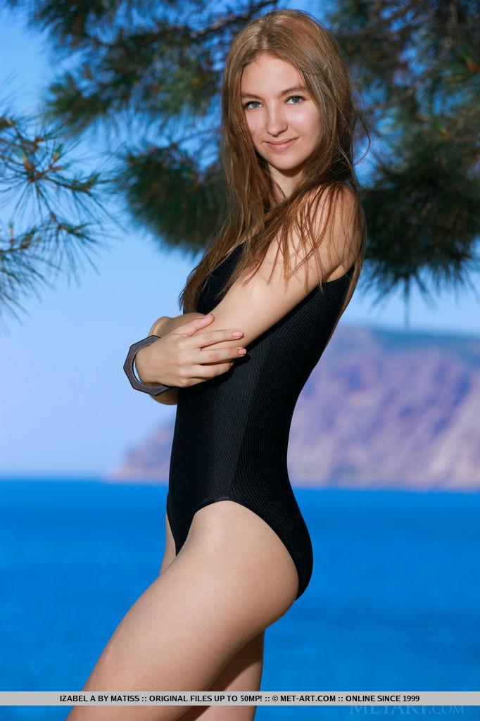 Раскрепощенная брюнетка позирует на берегу моря и с наслаждением ласкает красивую попку и демонстрирует кремовую киску