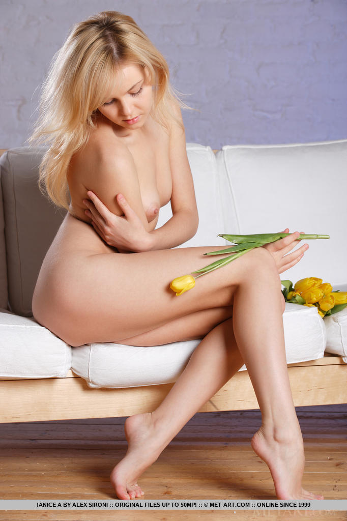Блондинка с букетом цветов в руках голой нежится на белоснежном диване и демонстративно раздвигает длинные ноги