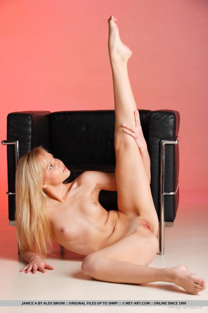 Длинноногая блондинка с розовой повязкой на ноге наслаждается своим телом в кожаном кресле перед вебкамерой