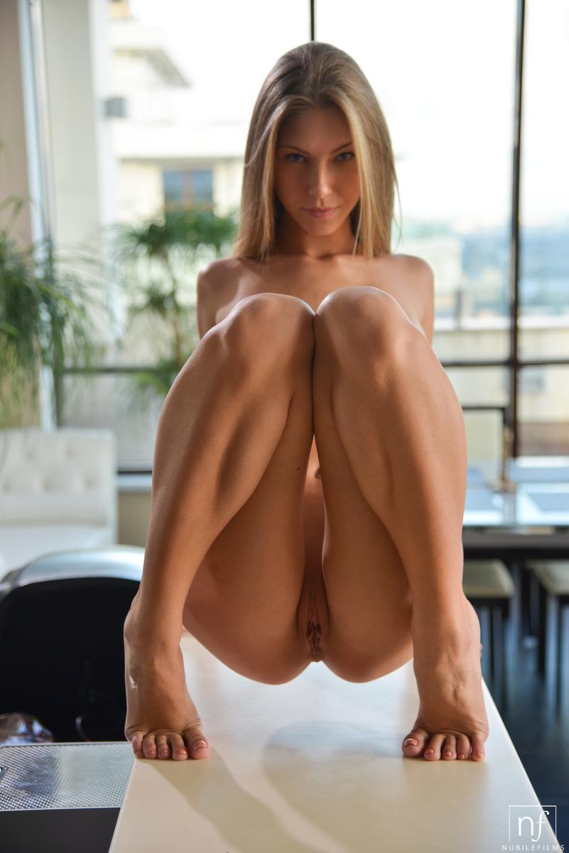 Девушка приспускает брюки и трахает себя пальцами в самых необычных позах в большой светлой комнате на столе