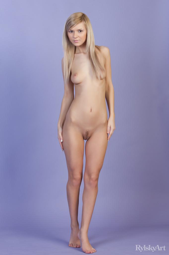 Длинноногая блондинка задирает одну ногу, чтоб показать стрижку на лобку и продемонстрировать большие половые губы