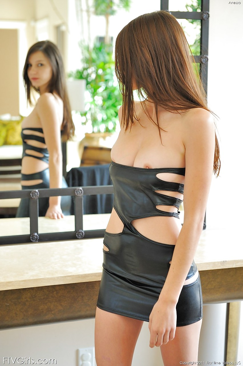 Брюнетка в кожаном платье обнажает красивую грудь и раздвигает ноги, чтоб показать влажную киску, в которую вставляет секс игрушку
