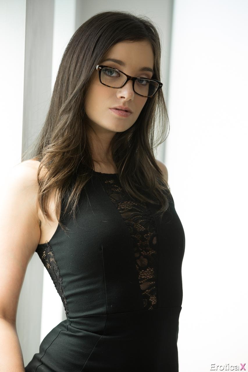 Худышка в очках эротично снимает обтягивающее платье и показывает татуировки на пикантных местах