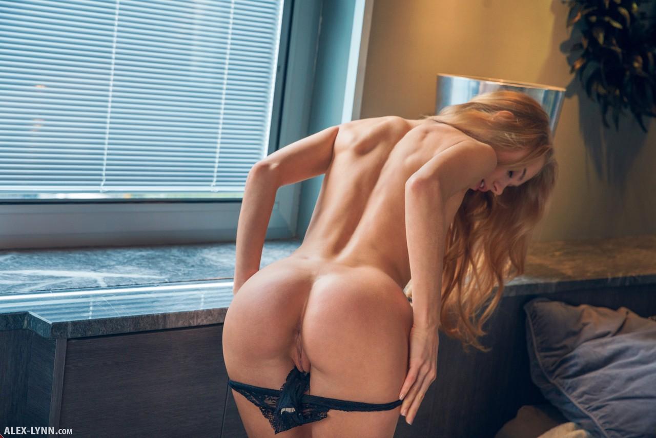 Девушка в кружевном белье лежит на столе у окна и нежно ласкает шикарное тело и вводит пальцы в мокрую пилотку