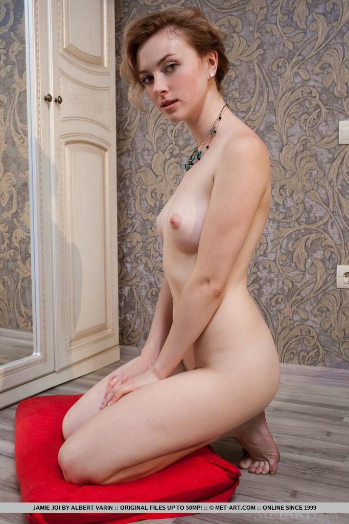 Голая девица с бусами на шее сидит на красном пуфе и показывает киску с большими розовыми половыми губами