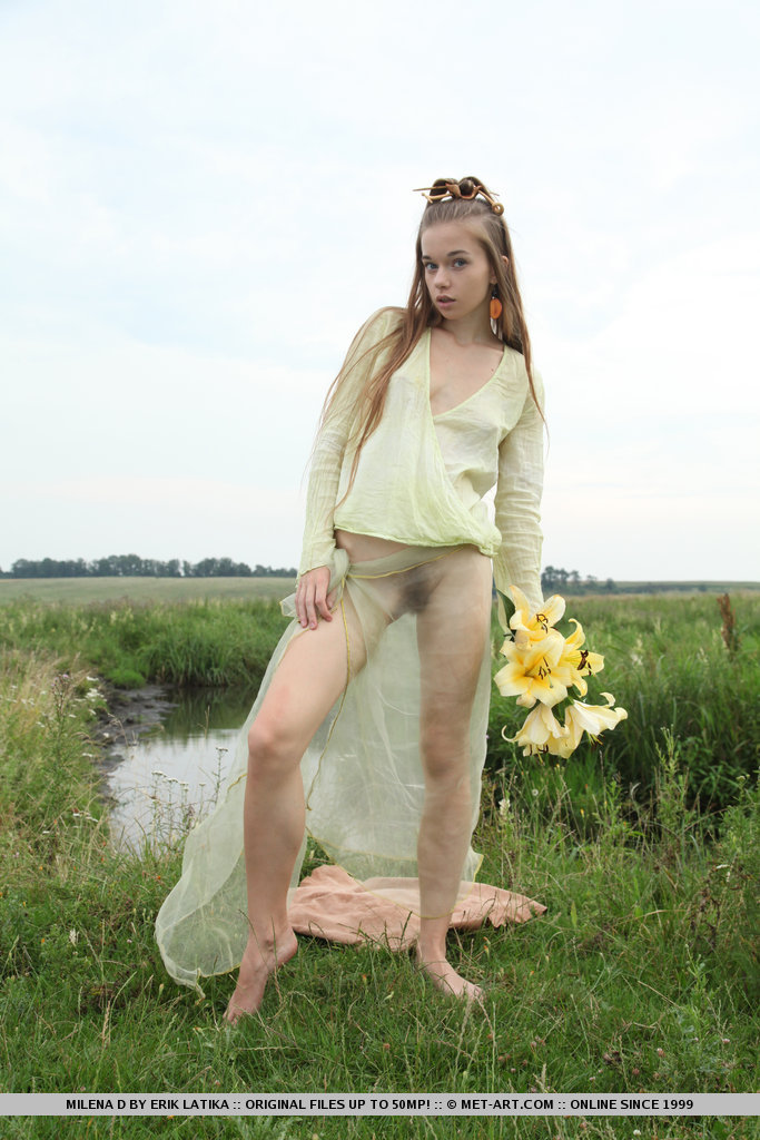Молоденькая красотка голой позирует на поляне возле озера и лилиями ласкает волосатую киску и красивую грудь