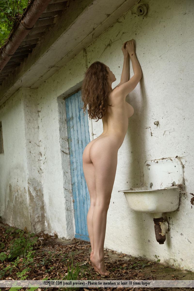 Девушка с растрепанными волосами прогуливается возле заброшенного дома и нежно ласкает обнаженное тело