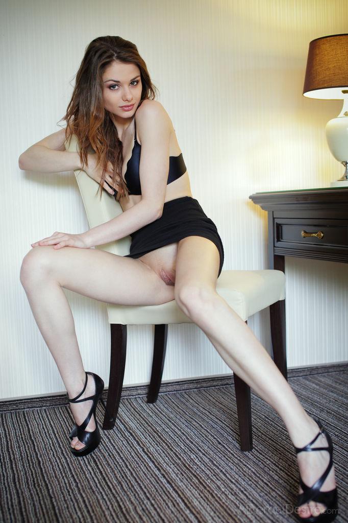 Брюнетка на высоких каблуках лежит на столе возле на стольной лампы и с пристрастием ласкает киску и облизывает пальцы