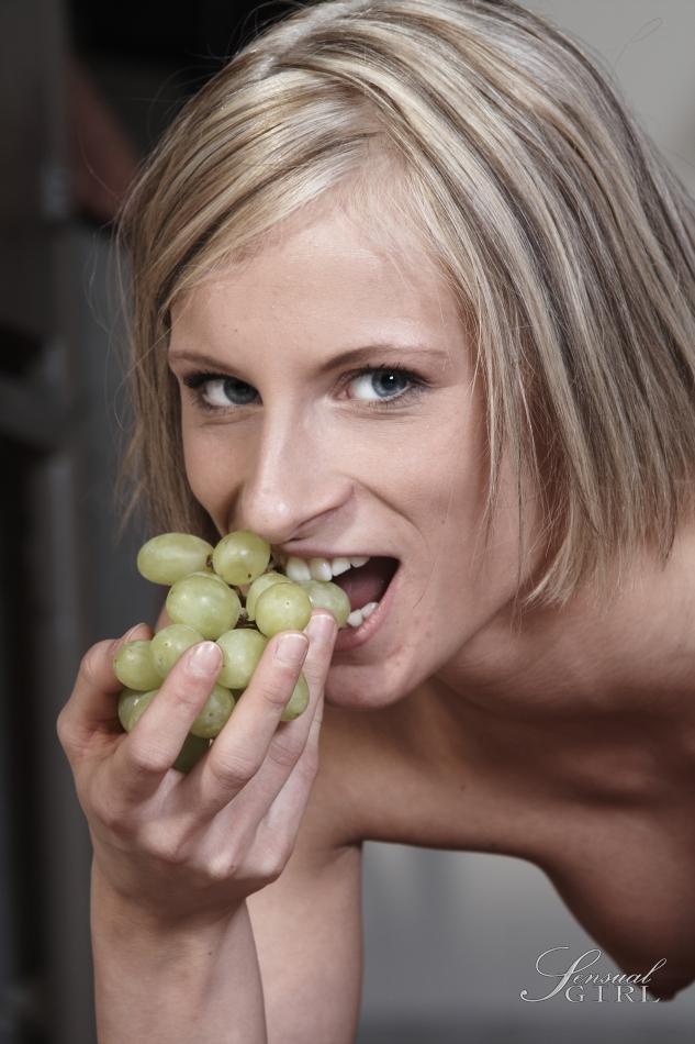 Блондинка медленно раздевается и эротично облизывает виноград и показывает небольшую грудь с торчащими сосками