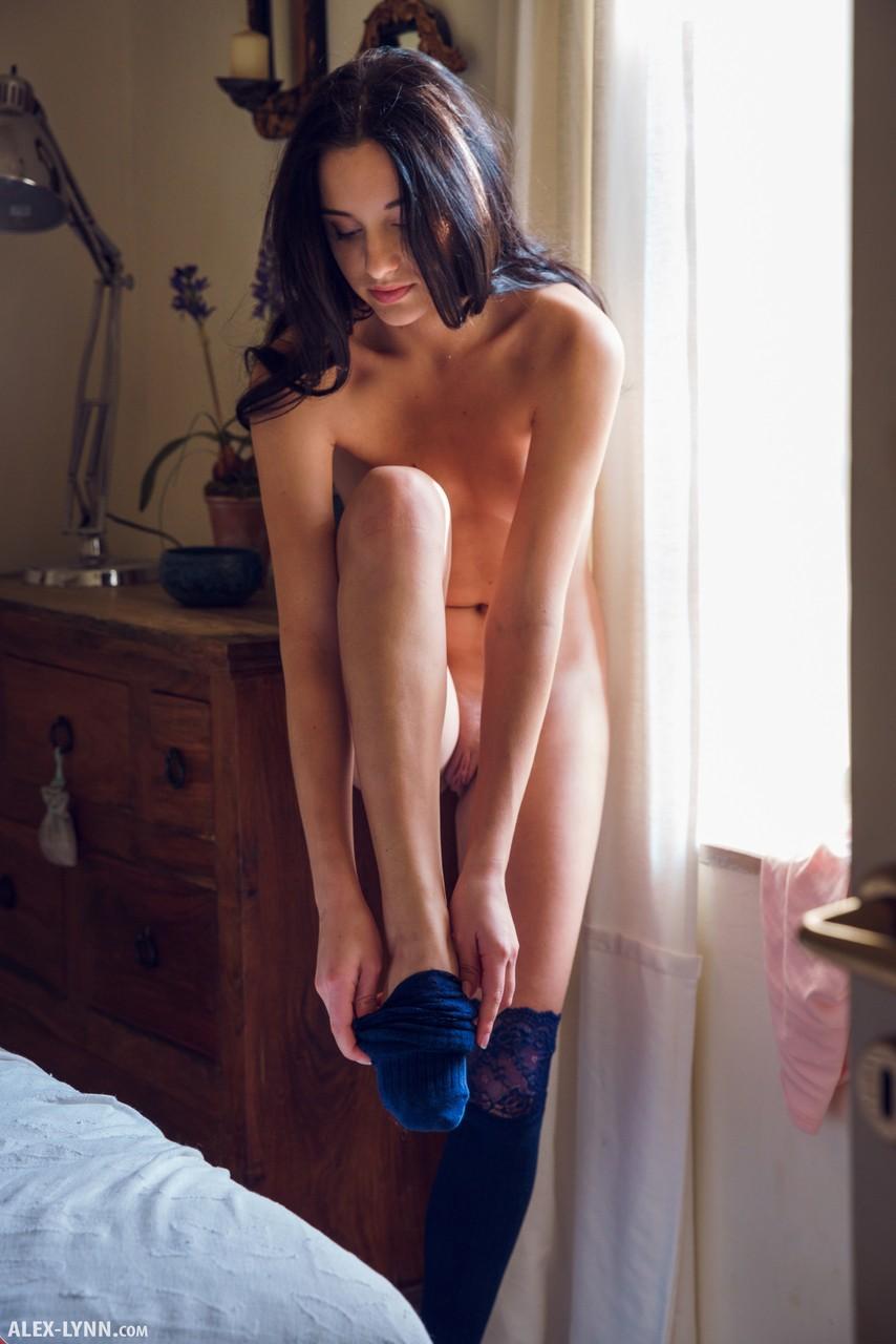 Голая худышка позирует возле окна и нежится на большой постели в спальне, при этом постоянно ласкает свое тело