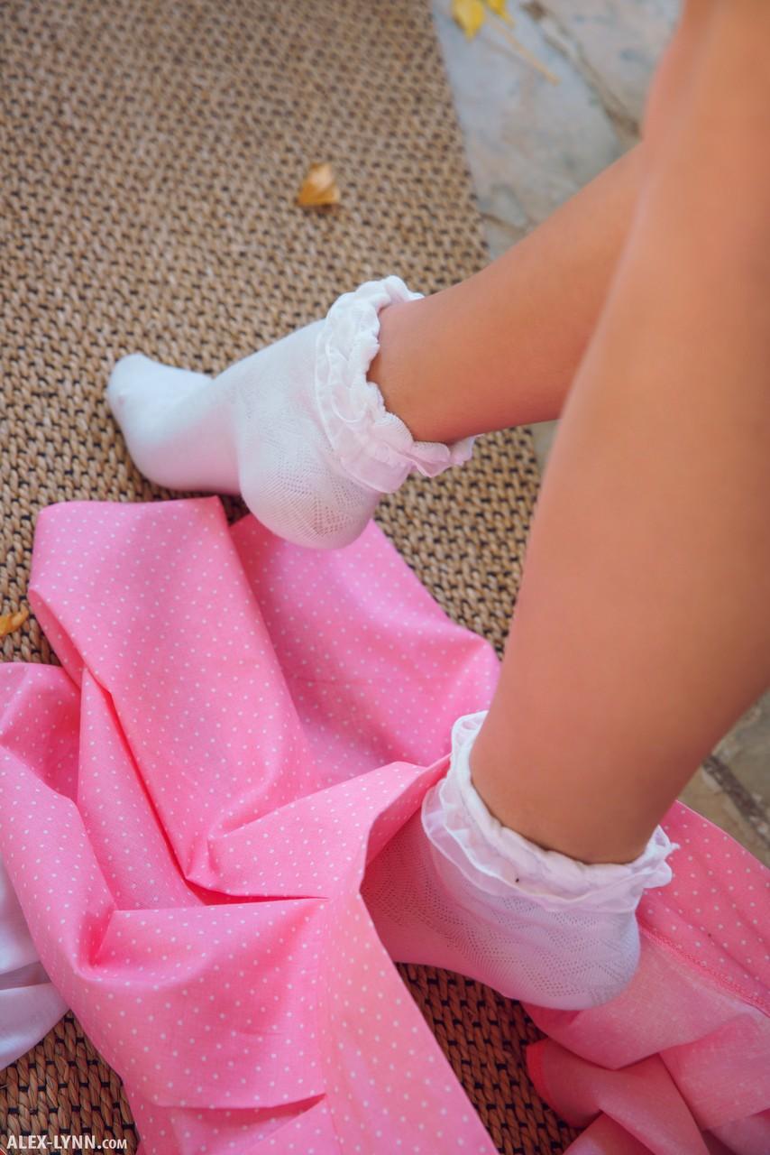Девушка в белых руках и в носках лежит на диване и пальцами сжимает кремовые соски и периодически ласкает киску