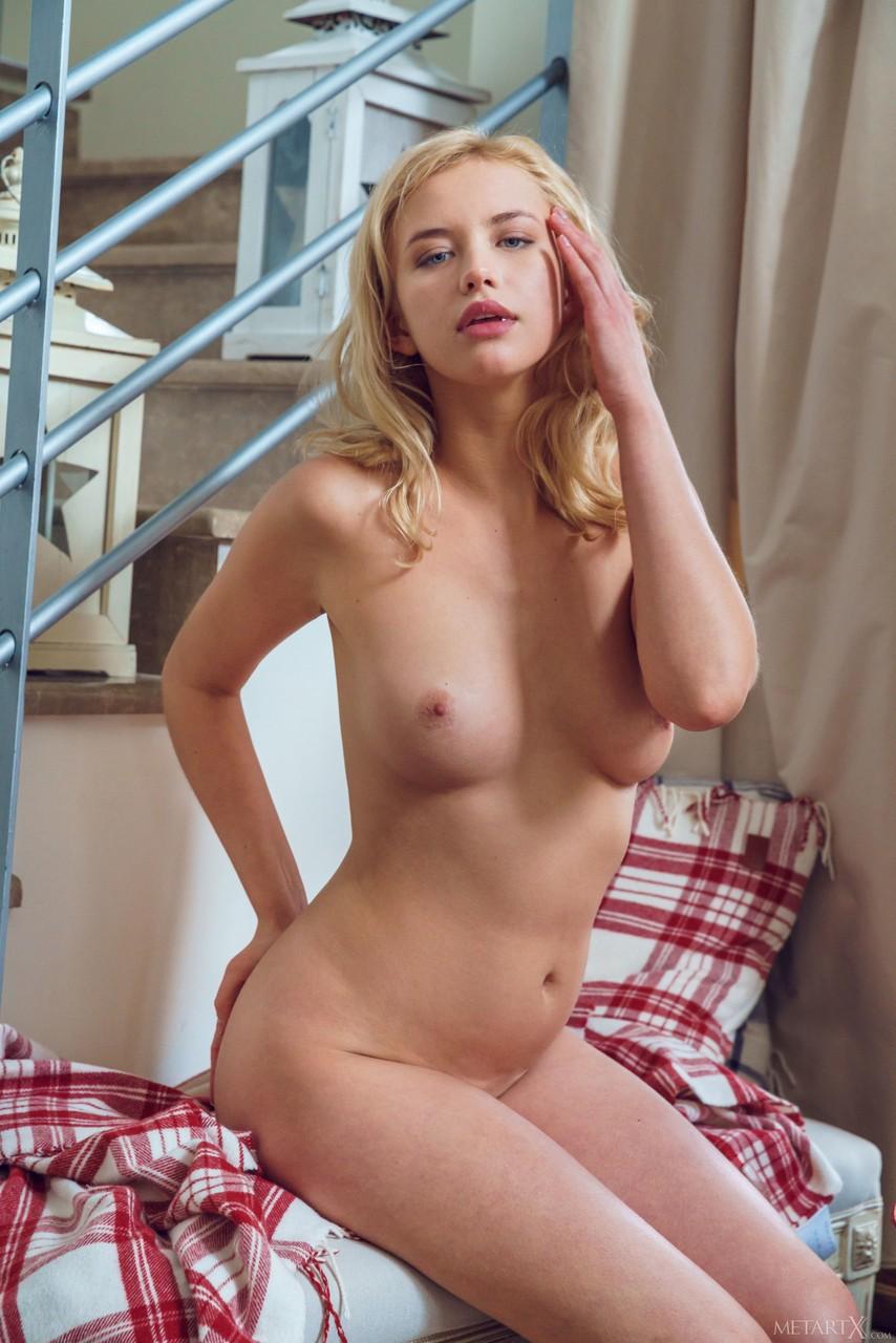 Светловолосая красотка позирует обнаженной и ласкает свое тело нежными руками. Она показывает упругую грудь и бритую щелочку.