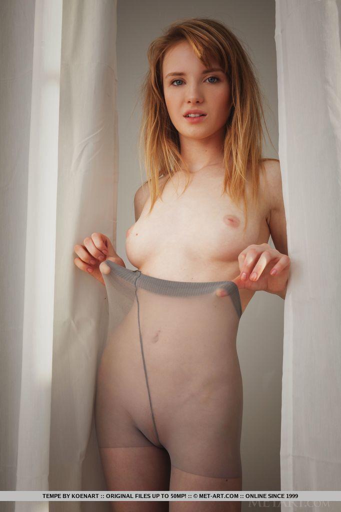 Девушка с небольшой грудью разрывает капроновые колготы и показывает свою розовую щелочку. Она хвастается упругой попкой и эротично извивается