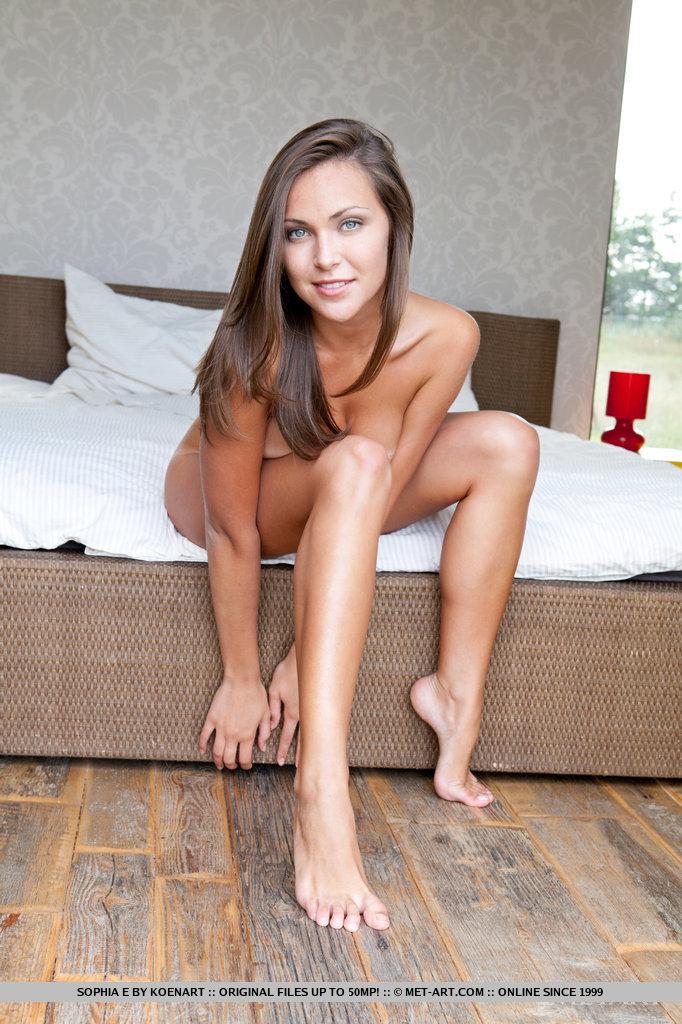Загорелая модель позирует на белоснежной постели и выставляет на показ все свои прелести. Она эротично мнет грудь и показывает попку