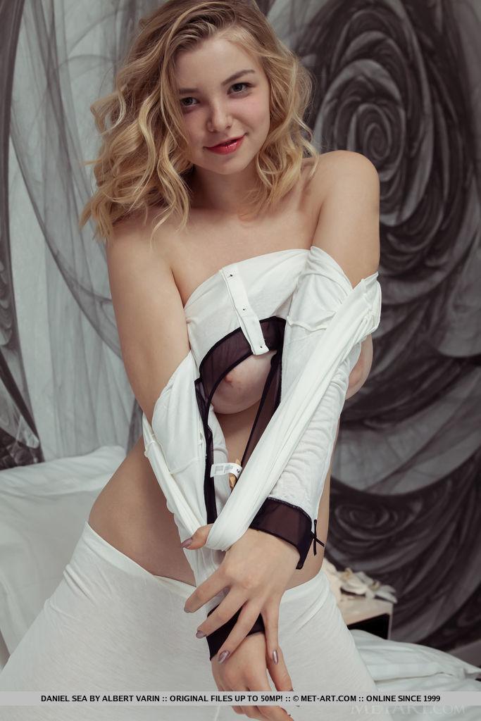 Симпатичная блондинка раздевается на белой постели. Она обнажает большую грудь, а немного погодя показывает бритую пилотку
