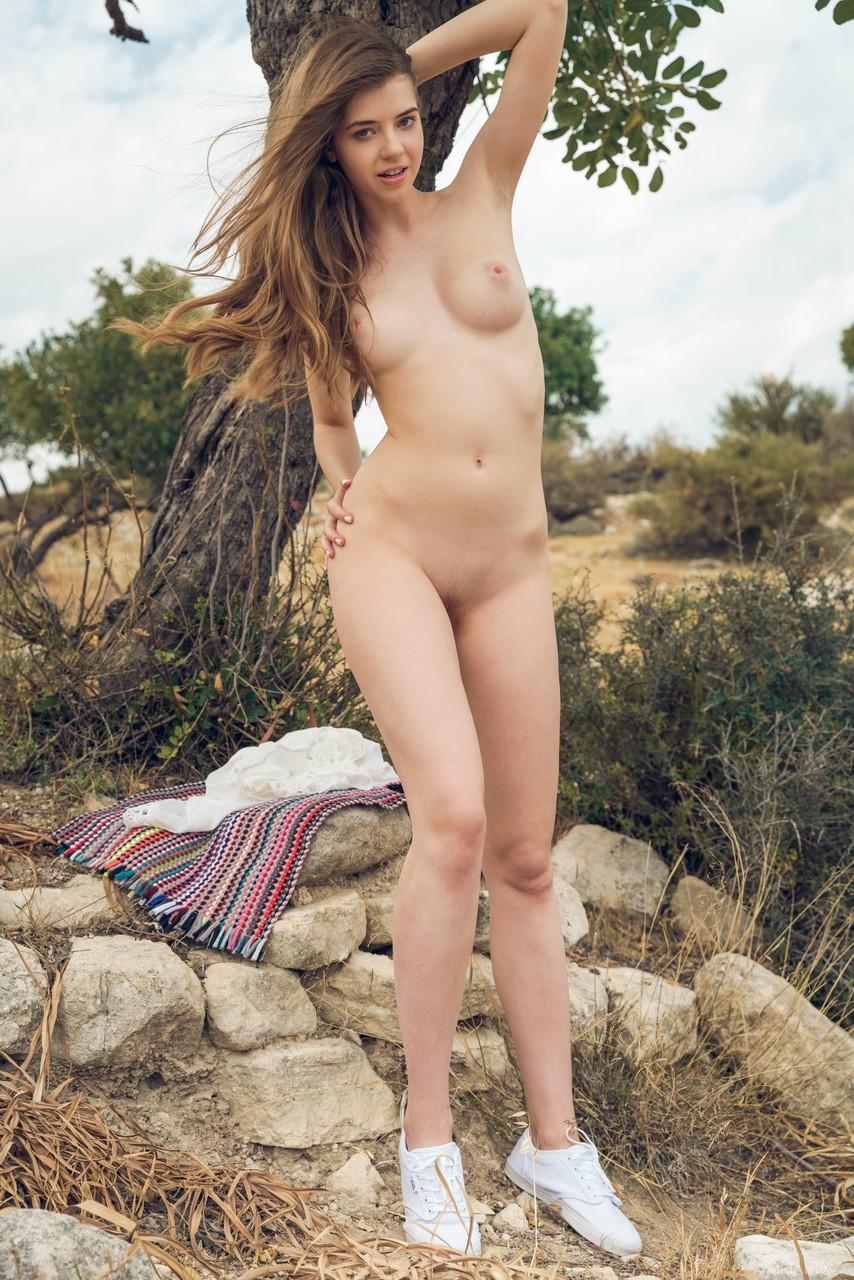 Стройная красотка позирует около дерева и нежно улыбается. Она демонстрирует натуральную грудь и прикрывает киску руками