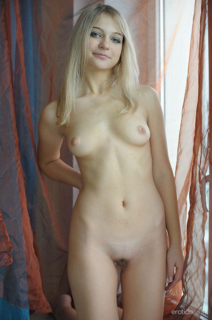 Голубоглазая блондинка позирует около окна совершенно обнаженной. Она мнет свою небольшую грудь нежными руками и эротично прогибает спину