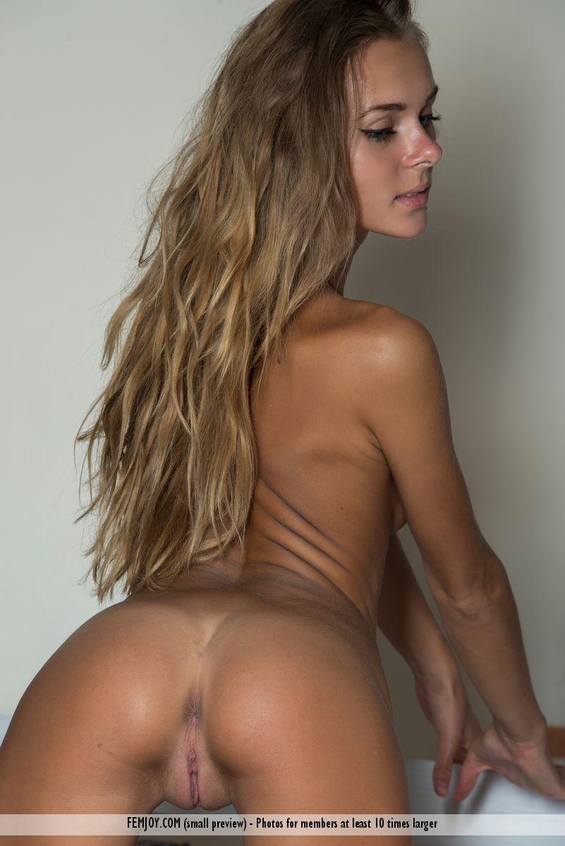 Загорелая девушка с демонстрирует своё гибкое тело. Она выставляет на показ упругую грудь и с удовольствием хвастается попкой