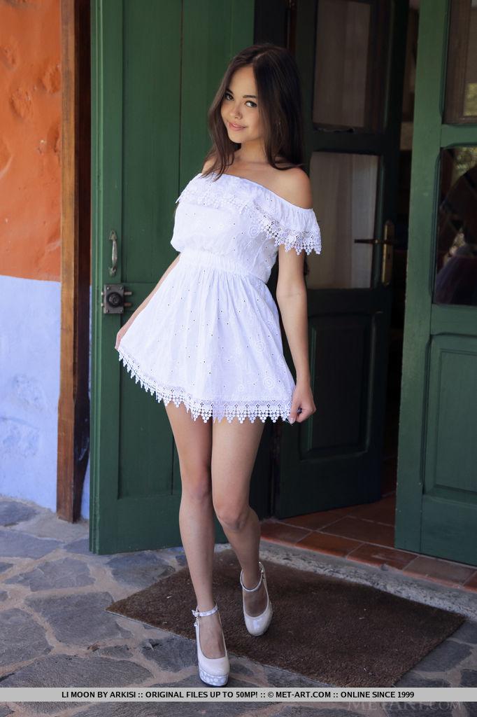 Милая азиатка снимает с себя белое платье по среди улицы и обнажает большую грудь. Она ловко разводит ноги на каблуках и хвастается киской