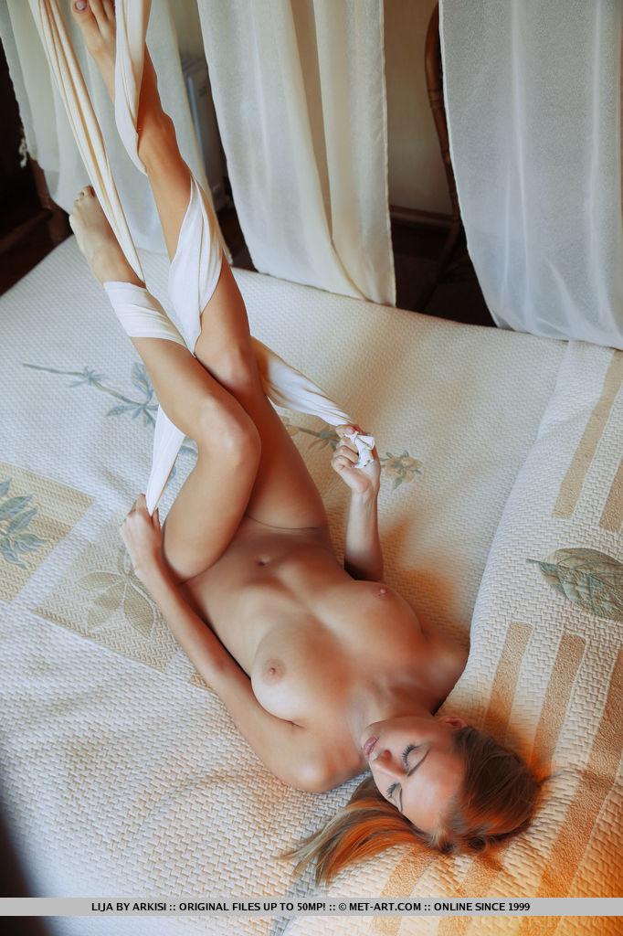 Страстная девушка снимает леопардовое платье и показывает большую грудь. Она позирует на постели и светит розовой щелочкой, нежно улыбаясь