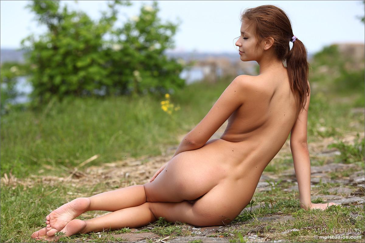 Стройная брюнетка раздевается на природе и демонстрирует волосатую киску и небольшие натуральные сиськи