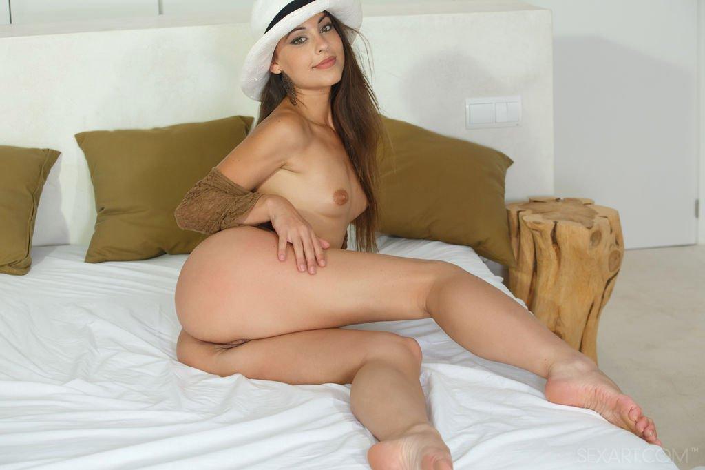 Брюнетка в шляпе раздевается на постели перед зеркалом и вставляет в анальную щелку небольшую секс игрушку
