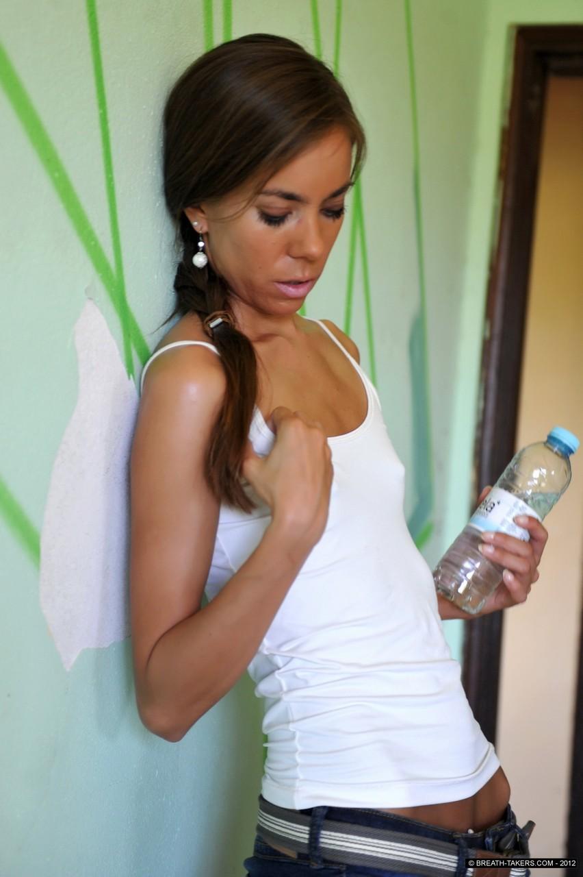 Плоскогрудая брюнетка пьет воду и проливает ее на себя так, что ее майка становится мокрой и видна небольшая грудь