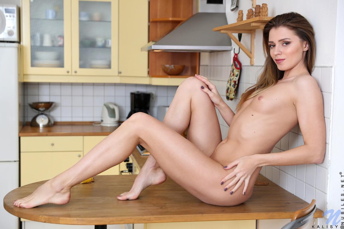 Девушка в коротком платье позирует на кухне и нежно ласкает кремовую киску лежа на кухонном столе