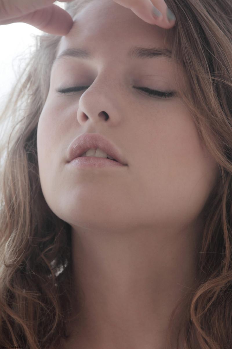 Девушка в обтягивающих чулках полуголой лежит на постели и крупным планом показывает упругую грудь второго размера