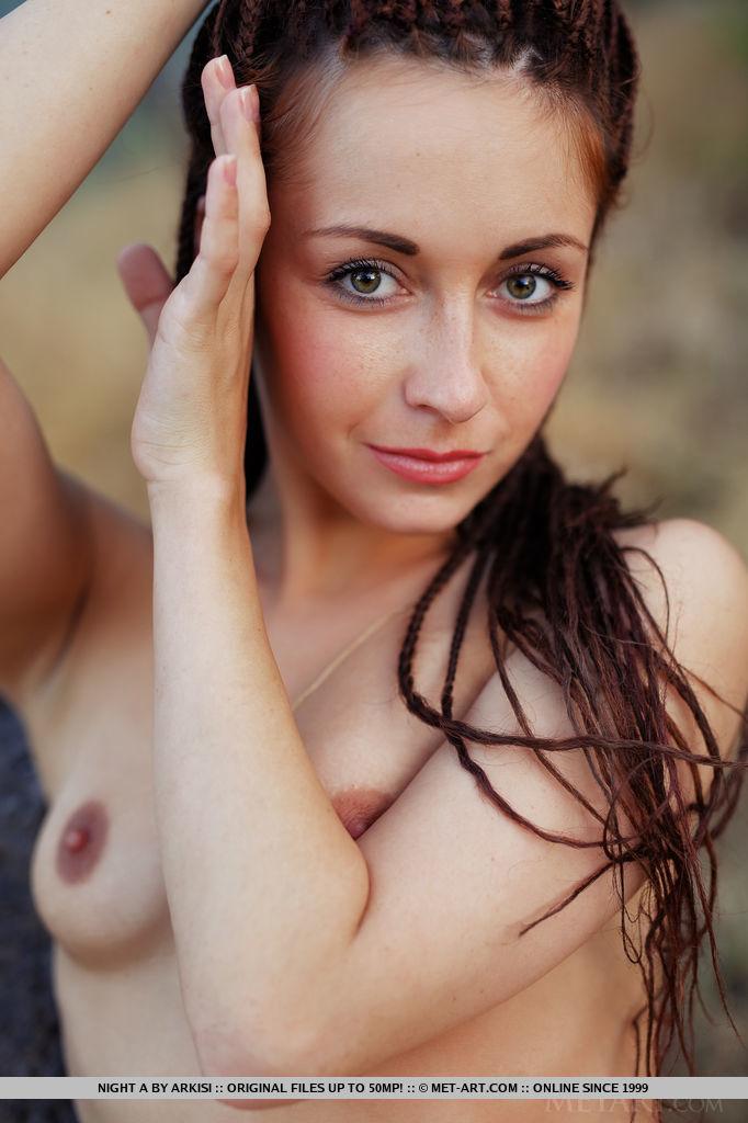 Худышка с дредами на голове показывает коричневые половые губы и позирует совершенно голой в лесу на большом камне