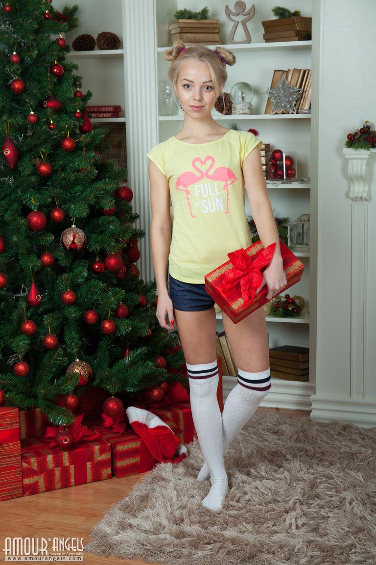 Плоскогрудая блондинка в чулках позирует возле рождественской елки и показывает маленькую грудь и лысую киску