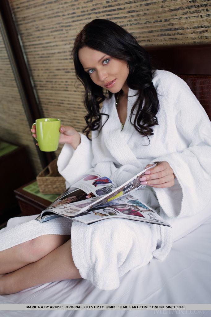 Блондинка в белоснежном халате с чашкой кофе в руках раздевается и демонстрирует хорошую растяжку и наслаждается своим телом