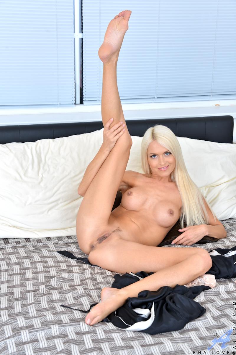 Блондинка с красивой грудью задирает ноги и обеими руками раздвигает половые губы, чтоб поиметь себя в щелку
