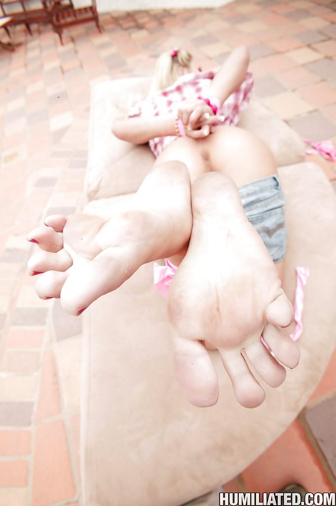 Связанная блондинка извивается на улице на небольшом камне и каждый раз ее пикантные места видны с разных сторон