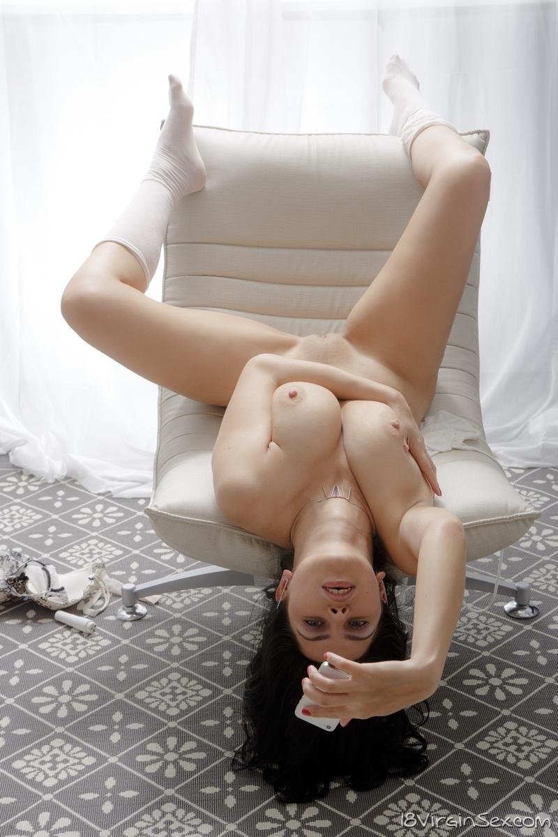 Брюнетка совершенно голой делает селфи в обнаженном виде и эротично пальцами ласкает кремовую киску и натуральную грудь