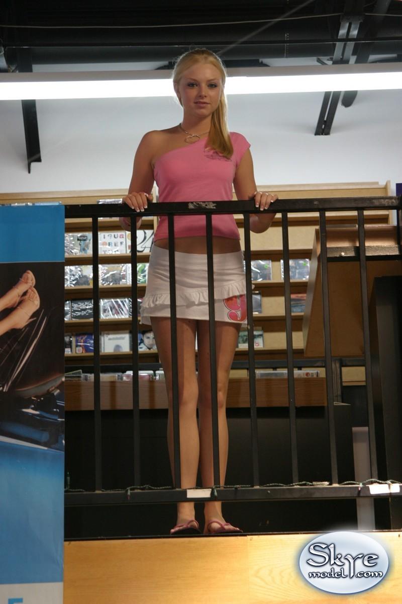Блондинка с красивой позирует на лестнице в таких позах и становится видно, что под ее юбкой нет нижнего белья