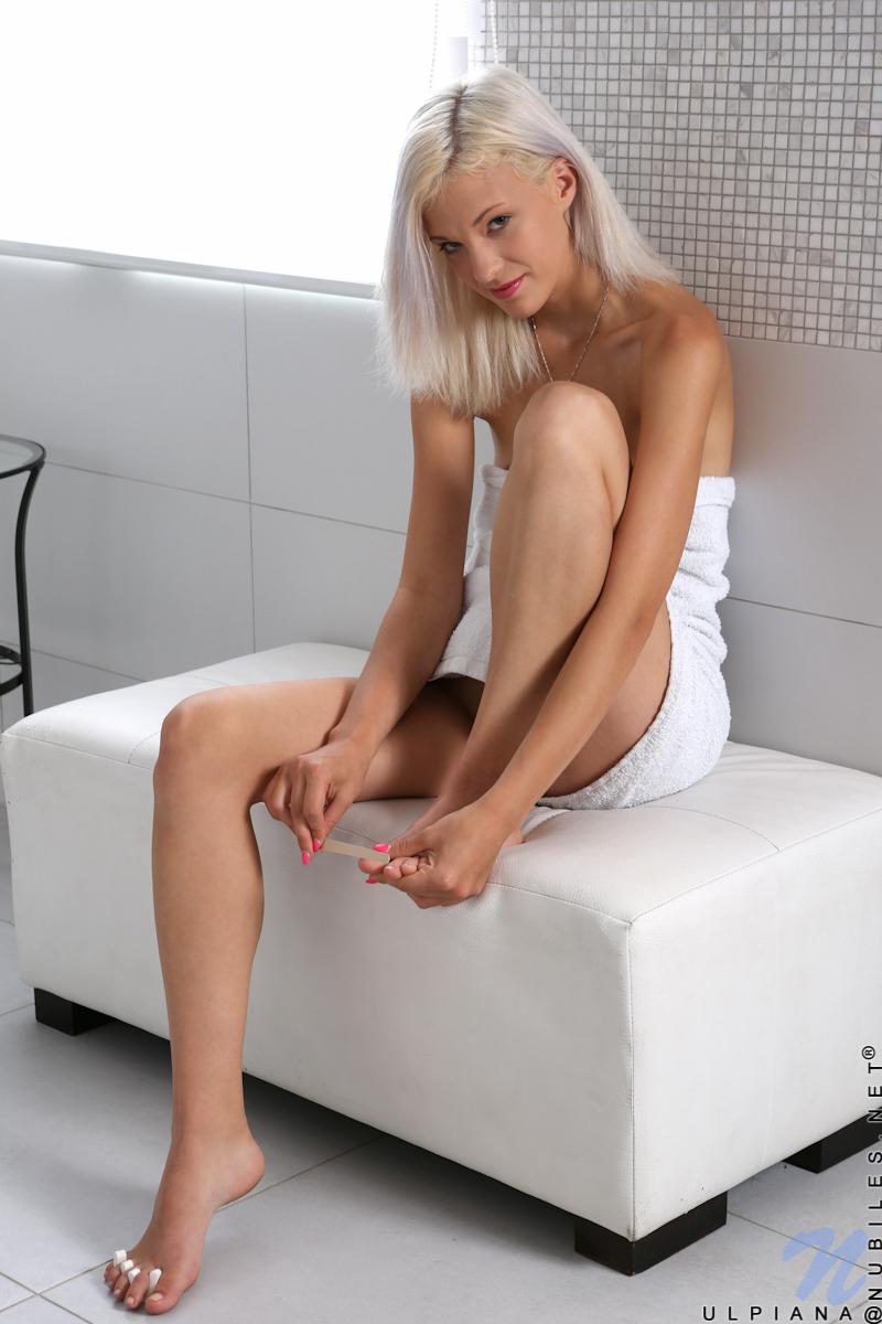Девушка с осветленными волосами нежится на небольшом пуфе и пальцами трет влажную киску и вводит пальцы в задницу