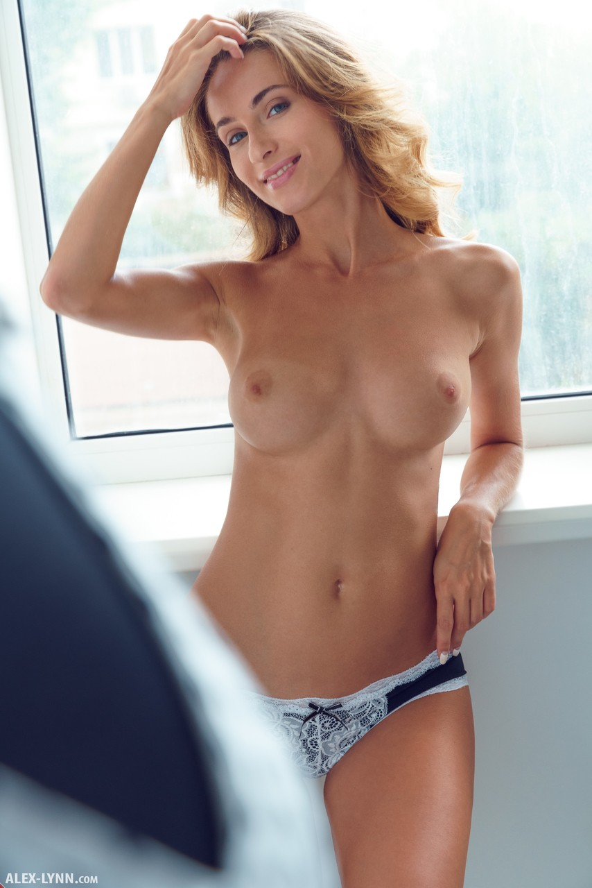 Девушка с красивой талией и шикарной грудью позирует в примерочной и пальцами киску с розовыми половыми губами