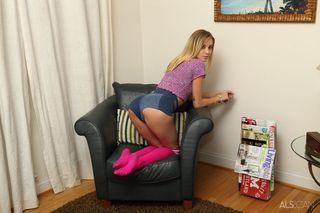 Блондинка в ярко-розовых чулках лежит в мягком кресле и пальцами растягивает гладко выбритую пилотку крупным планом