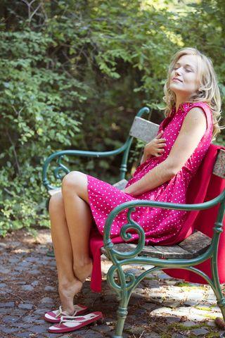 Светловолосая девушка в розовом сарафане отдыхает на природе и обнажает небольшую грудь. Позже она нежно ласкает свою киску пальцами