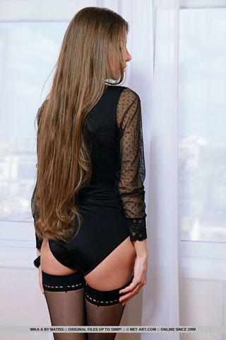 Девушка с распущенными волосами позирует на большой постели и длинным ожерельем прикрывает кремовую киску